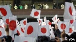 Kaisar Akihito (tengah kiri), permaisuri Michiko (tengah kanan) dan anggota keluarga kekaisaran Jepang melambaikan tangan kepada warga yang memadati halaman Istana Kekaisaran Tokyo dalam perayaan tahun baru (2/1).