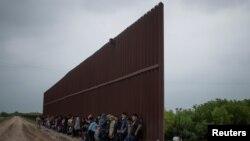 Migrantes centroamericanos se alinean a lo largo del muro fronterizo mientras esperan rendirse a la patrulla fronteriza de EE.UU., 2 de abril de 2019.