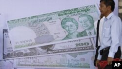 បុរសកម្ពុជាម្នាក់ដើរនៅជិតរូបថតរូបិយវត្ថុផ្សេងៗ ក្នុងអំឡុងពិធីបើកសម្ពោធទីស្នាក់ការផ្សារមូលបត្រកម្ពុជា (Cambodia Securities Exchange) ក្នុងទីក្រុងភ្នំពេញកាលពីថ្ងៃច័ន្ទទី១១ខែកក្កដាឆ្នាំ២០១១។
