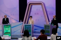Hong Kong chief executive candidates, former Chief Secretary Carrie Lam, center, former Financial Secretary John Tsang Chun-wah, left, and former judge Woo Kwok-hing attend a chief executive election debate in Hong Kong, March 14, 2017.