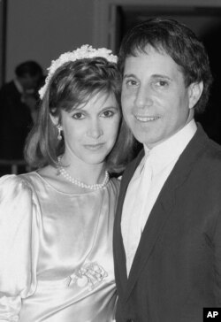 FILE - Actress Carrie Fisher and singer Paul Simon pose in a doorway of the midtown New York City apartment where their wedding reception was in progress, Aug. 16, 1983.
