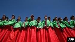 Jeunes femmes en robe hanbok assistant à une cérémonie traditionnelle pour marquer l'âge adulte au village Namsan Hanok à Séoul. La cérémonie marque l'âge de 19 ans, lorsqu'une personne est légalement en mesure de faire des choix de vie et de voter. (Ed Jones/AFP/20 mai 2019)