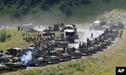 FILE - A column of Russian armored vehicles on its way to the South Ossetian capital Tskhinvali in the Georgian breakaway region, South Ossetia, Aug. 9, 2008.