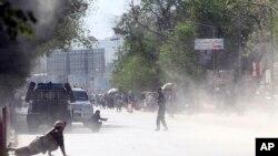 کابل میں ہونے والے دوسرے دھماکے کے فوری بعد کا منظر جس سے بچنے کے لیے ایک سکیورٹی اہلکار اور ایک عام شہری زمین پر لیٹے ہوئے ہیں۔