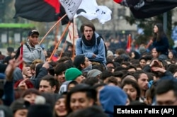Youths take part in a march demanding the government overhaul the education funding system that would include canceling student loan debt, in Santiago, Chile, Wednesday, June 21, 2017.