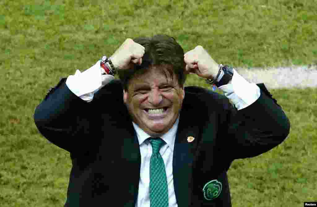 Mexico's coach Miguel Herrera celebrates after his team scores its third goal during their match against Croatia at the Pernambuco Arena in Recife, June 23, 2014.