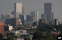 A smoky haze envelopes the skyscrapers and Rocky Mountains that usually can be seen as a backdrop to the city from a high-rise building, Aug. 20, 2018, in Denver.