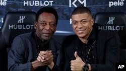 Pelé, la légende du football mondial (à g.), avec le footballeur français Kylian Mbappe à Paris, le 2 avril 2019. (AP Photo)