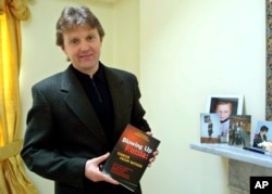 """FILE - Alexander Litvinenko, former KGB spy and author of the book """"Blowing Up Russia: Terror From Within,"""" is photographed at his home in London, May 10, 2002."""