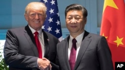"FILE - President Donald Trump and Chinese President Xi Jinping shake hands as they arrive for a meeting on the sidelines of the G-20 Summit in Hamburg, Germany, July 8, 2017. Ambassador Cui said that both leaders have ""set a constructive tone"" in their bilateral relationship."