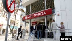 Depositors wait to enter a branch of Laiki Bank in Nicosia, March 29, 2013.