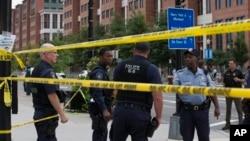 Polisi Washington berjaga di jalan M, Washington DC, dekat lokasi penembakan di gedung Angkatan Laut AS (Navy Yard), Senin (16/9).