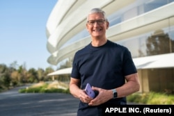 Tim Cook holds purple iPhone