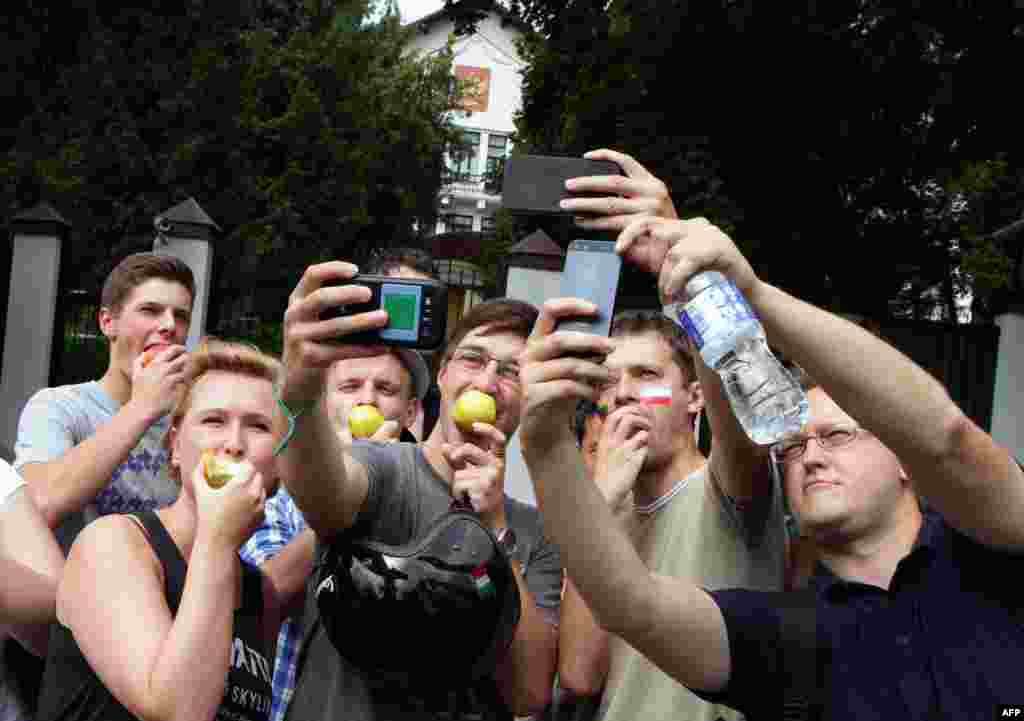 "Lithuanians take ""selfies"" as they eat Polish apples in front of the Russian Embassy in Vilnius.  They are showing support for Poland after Russia restricted apple imports from Poland."