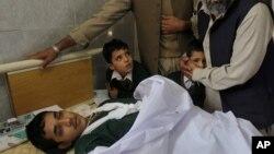 Pria Pakistan menghibur anak-anak sekolah yang menemani rekan mereka yang terluka akibat serangan di Peshawar, Pakistan (16/12).