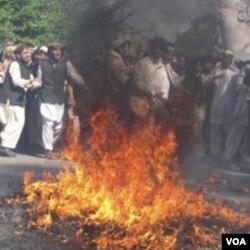 Para demonstran melakukan aksi pembakaran bendera AS di Jalalabad, dalam aksi protes atas pembakaran al-Quran di AS untuk hari ketiga, Minggu (3/4).