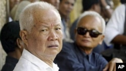 Former Khmer Rouge leaders Khieu Samphan, left, and Nuon Chea, right, look on during the funeral for Khieu Ponnary, the first wife of Khmer Rouge leader Pol Pot, in 2003.