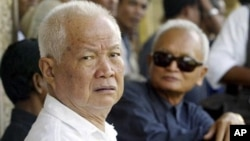 Former Khmer Rouge leaders Khieu Samphan, left, and Nuon Chea, right, look on during the funeral for Khieu Ponnary, the first wife of Khmer Rouge leader Pol Pot, file photo.