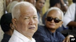 Former Khmer Rouge leaders Khieu Samphan, left, and Nuon Chea, right, look on during the funeral for Khieu Ponnary, the first wife of Khmer Rouge leader Pol Pot, in 2003, file photo.