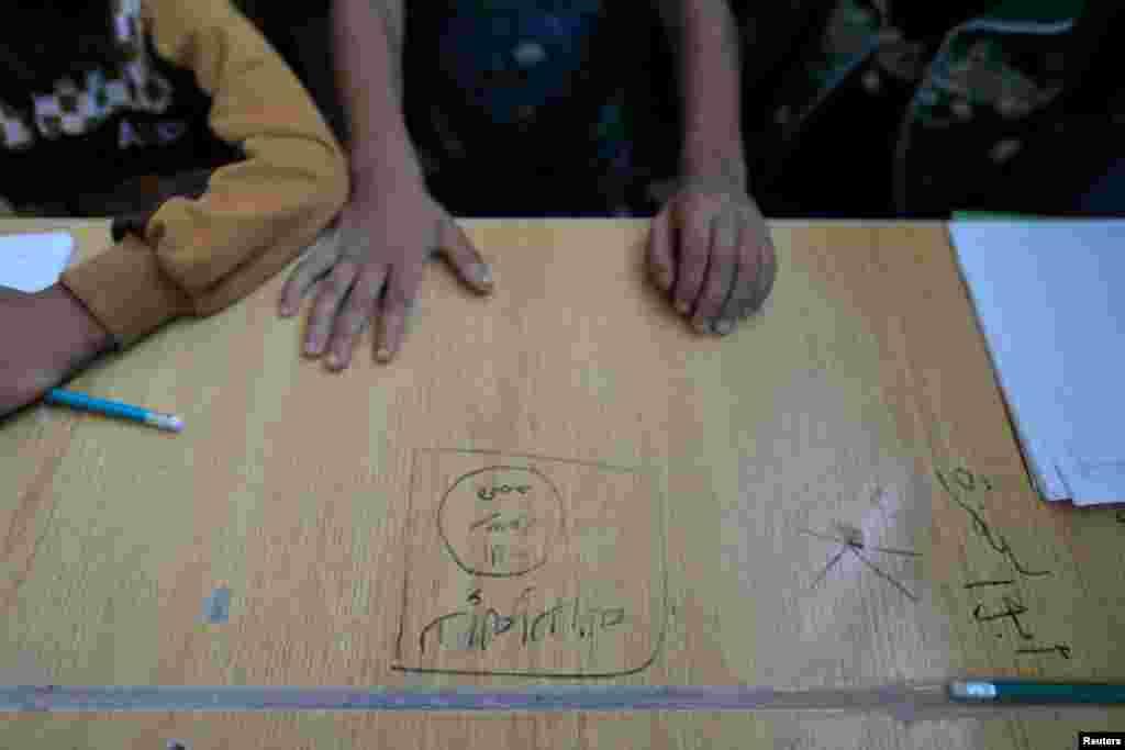 رقہ کے ایک اسکول میں میز پر داعش کا نشان بنا ہوا ہے