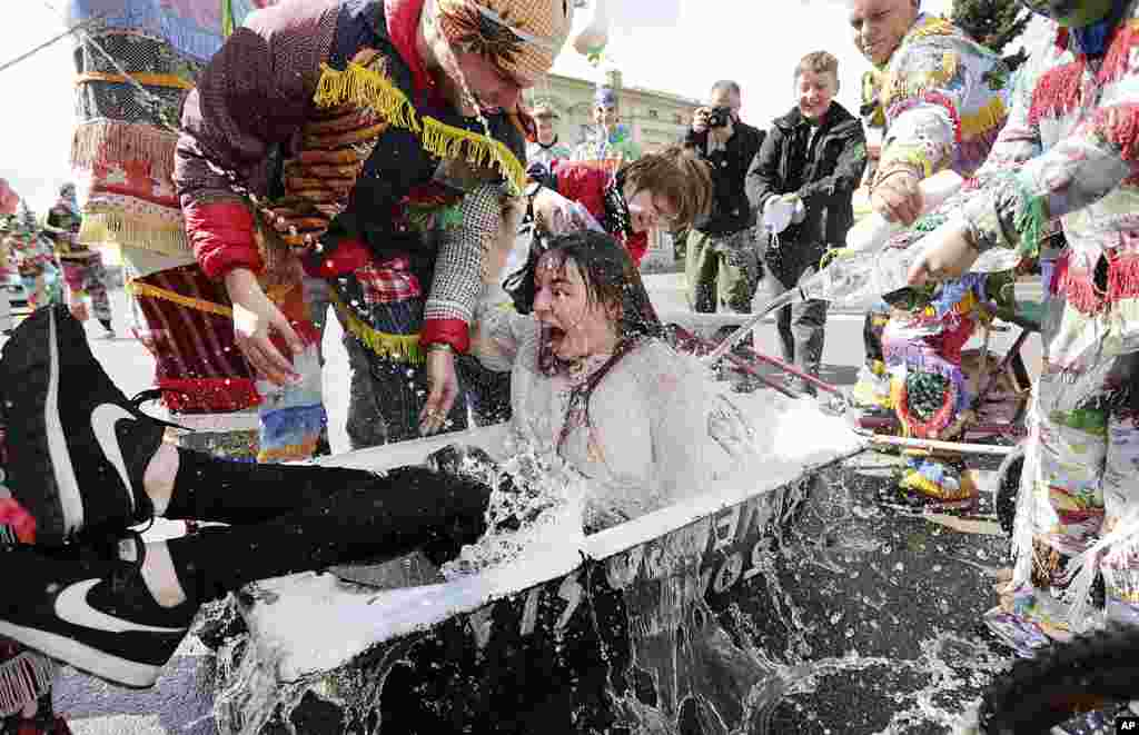 A girl is splashed with water by boys following a Polish Wet Easter Monday tradition, in Wilamowice, Poland.