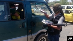 FILE - A fighter with the Islamic State distributes a copy of the Quran, Islam's holy book, to a driver in Mosul, Iraq, June 22, 2014. Islamic scholars in Bangladesh are denouncing activities of the Islamic State.
