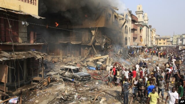 People gather at the site of a fire, a result of an explosion at a warehouse where witnesses say fireworks were stored, December 26, 2012.