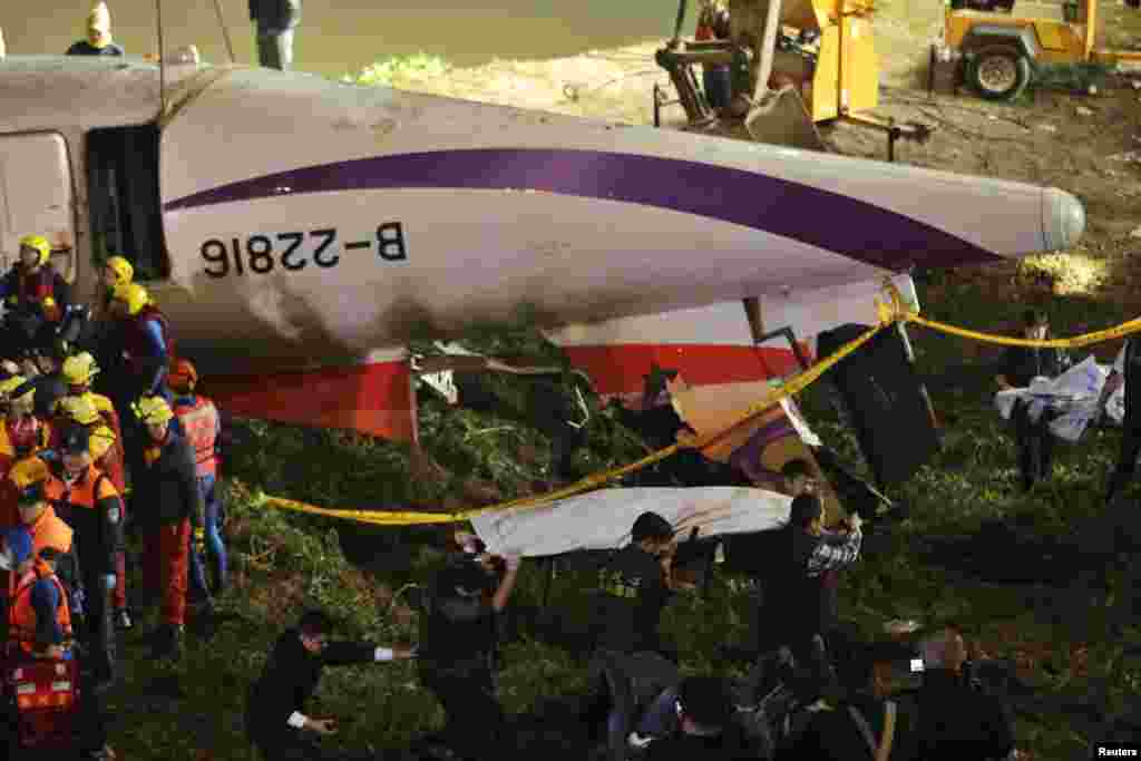 Rescuers carry one body in a bag away after a TransAsia Airways plane crash landed in a river, in New Taipei City.