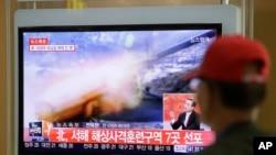 一名男子在首尔某地铁站观看有关朝鲜军事演习的电视新闻。(2014年3月31日)