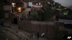 FILE - Afghans carry supplies to their home at dusk in Kabul, Afghanistan, Sept. 14, 2021.