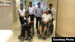 Cambodian opposition lawmakers Nhay Chamroeun (L) and Kong Saphea are seen in wheelchairs at Phyathai Hospital in Bangkok October 27, 2015, a day after being beaten by assailants in Phnom Penh, Cambodia. (Courtesy - Nhay Chamroeun).