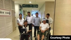 Cambodian opposition​ CNRP lawmakers Nhay Chamroeun and Kong Saphea are seen in wheelchairs at Phyathai hospital in Bangkok on Tuesday, October 27, 2015 after being beaten by protesters in Phnom Penh, Cambodia on Monday. (Courtesy of Nhay Chamroeun)