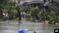 一名菲律宾男子用储水容器在洪水中漂浮