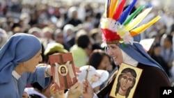 Kaluđerice drže ikone sa likom Kateri Tekakvite