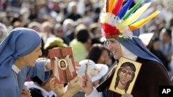 """Dua orang biarawati di Vatikan memegang gambar Kateri Tekakwitha orang pribumi Amerika pada abad ke 17 yang dikenal sebagai """"Lily of the Mohawks"""" dalam upacara kanonisasi hari Minggu (21/10)."""