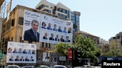 Posters with Lebanese parliament candidates are seen on a building in Beirut, Lebanon, April 23, 2018.