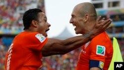 Pemain Belanda Memphis Depay (kiri) merayakan kemenangan atas Chile dengan anggota tim Arjen Robben di Sao Paulo (23/6).