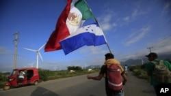 Un migrante lleva las banderas de México y Honduras, mientras un conductor de moto se detiene para tomar una foto, en Juchitán, estado de Oaxaca, el 1 de noviembre de 2018.