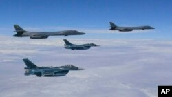 지난달 8일 미국 괌 공군지기에서 출격한 미 공군 소속 장거리전략폭격기 B-1B 2 기가 일본 남부 규슈 상공에서 일본 항공자위대 소속 F-2 전투기 2기와 비행훈련을 하고 있다. (자료사진)