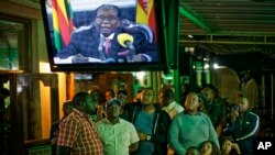 FILE: Zimbabweans watch a televised address to the nation by President Robert Mugabe at a bar in downtown Harare, Zimbabwe, Nov. 19, 2017.