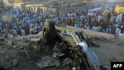 Des badauds autour des restes d'un avion de ligne nigérian tombé dans un quartier résidentiel bondé de Kano, le 5 mai 2002.