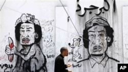 A man passes graffiti caricatures related to Moammar Gadhafi and Brega, during a funeral in Benghazi, April 19, 2011