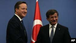 British Prime Minister David Cameron, left, and his Turkish counterpart, Ahmet Davutoglu, conclude a news conference in Ankara, Dec. 9, 2014.