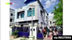 People walk out from a house believed to have been raided by security forces, in Mandalay, Myanmar, June 22, 2021 in this screen grab taken from a REUTERS TV video.