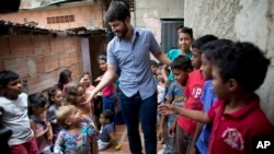 Roberto Patino greets children at a children's center in the La Vega neighborhood of Caracas, Venezuela, Aug. 26, 2018.