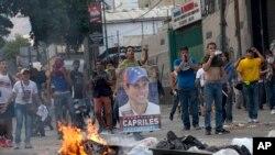 ພວກປະທ້ວງ ຖືປ້າຍຜູ້ນໍາຝ່າຍຄ້ານ ທ່ານ Henrique Capriles ກໍາລັງປະເຊີນໜ້າກັບເຈົ້າໜ໊າທີ່ຕໍາຫລວດ