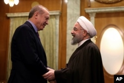 FILE - Turkey's President Recep Tayyip Erdogan, left, and Iran's President Hassan Rouhani greet each other before a meeting with Russia's President Vladimir Putin, in Sochi, Russia, Nov. 22. 2017.