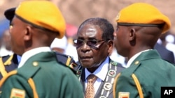 Zimbabwean President Robert Mugabe inspects the guard of honour during a ceremony in Harare, Monday Aug. 10, 2015. (AP Photo/Tsvangirayi Mukwazhi)