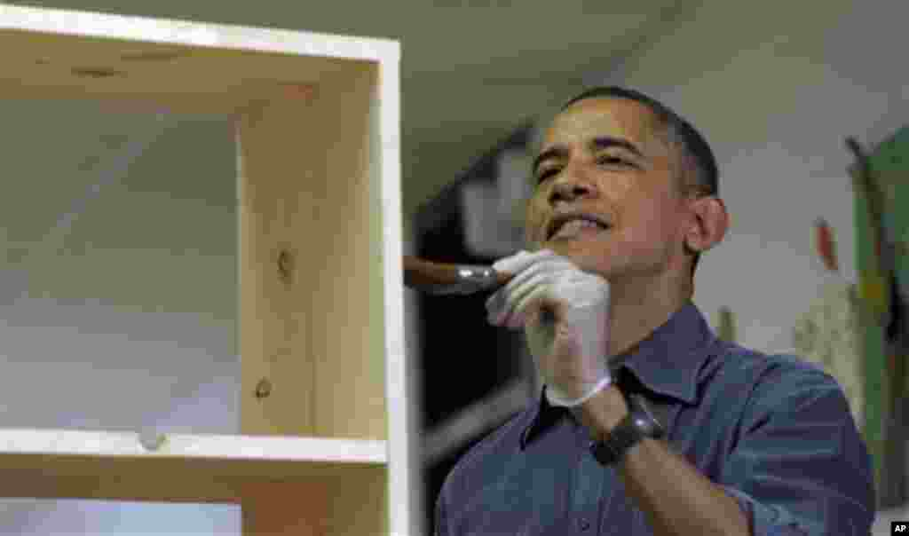 President Barack Obama stains a bookshelf at Burrville Elementary School as the first family participated in a community service project for the National Day of Service, part of the 57th Presidential Inauguration, in Washington, January 19, 2013.