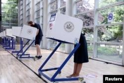 Perwakilan AS. Alexandria Ocasio-Cortez dan rekannya, Riley Roberts, memberikan suara dalam pemilihan awal Kongres Partai Demokrat di borough Bronx, New York City, 20 Juni 2020. (Foto: dok).